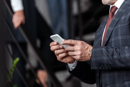 Photo pour Cropped view of businessman using smartphone in office - image libre de droit