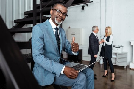 Photo for Selective focus of cheerful african american man showing thumb up near partners in office - Royalty Free Image