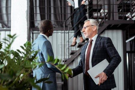 Photo pour Vue bas d'angle de l'homme d'affaires serrant la main avec le partenaire américain africain - image libre de droit