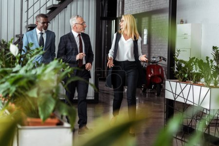 Photo for Selective focus of businesswoman gesturing while walking with multicultural partners in office - Royalty Free Image
