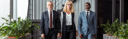 Photo for Panoramic shot of confident blonde businesswoman standing with handsome multicultural partners in office - Royalty Free Image