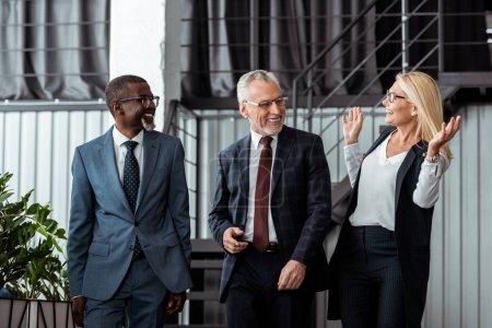 Foto de Mujer de negocios feliz gestuing mientras sonríe con socios multiculturales en la oficina - Imagen libre de derechos