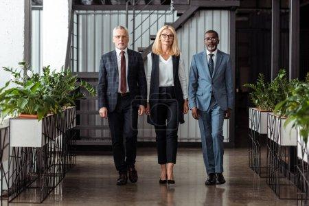 Photo pour Femme d'affaires blonde confiante marchant avec de beaux associés multiculturels dans le bureau - image libre de droit