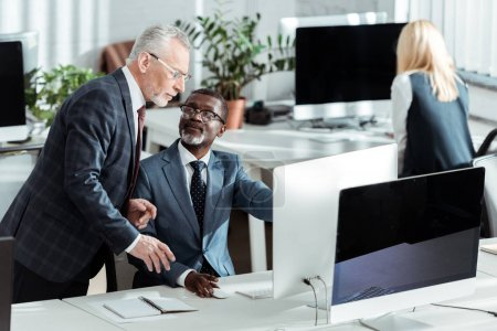 Photo for Selective focus handsome african american businessman looking at coworker in office - Royalty Free Image