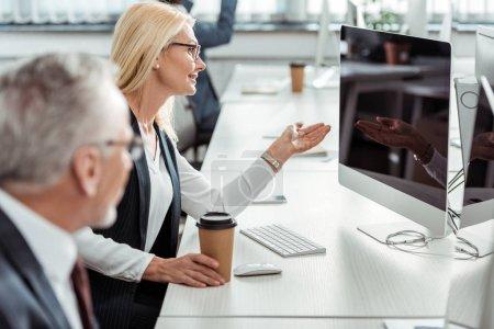 enfoque selectivo de mujer de negocios rubia en gafas de gestos mientras mira el monitor de la computadora cerca de compañero de trabajo