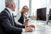 selective focus of blonde businesswoman in glasses gesturing while looking at coworker