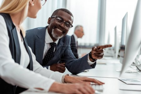 selective focus of cheerful african american businessman pointing with finger at computer monitor near blonde coworker