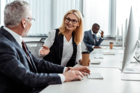 Photo for Selective focus of cheerful blonde woman holding paper cup and gesturing while looking at man in office - Royalty Free Image