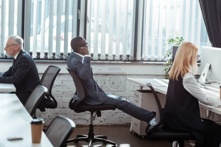 Photo for Multicultural businessmen and blonde businesswoman working in modern office - Royalty Free Image