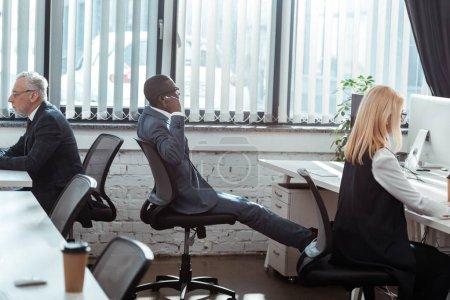Photo pour Hommes d'affaires multiculturels et femme d'affaires blonde travaillant dans le bureau moderne - image libre de droit