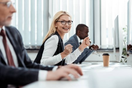 Photo for Selective focus of cheerful businesswoman smiling near men in office - Royalty Free Image