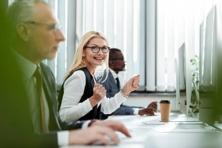 Photo for Selective focus of happy blonde businesswoman smiling and gesturing near men in office - Royalty Free Image