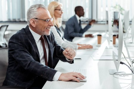 Photo pour Foyer sélectif de l'homme d'affaires heureux souriant et faisant des gestes près des collègues multiculturels dans le bureau - image libre de droit