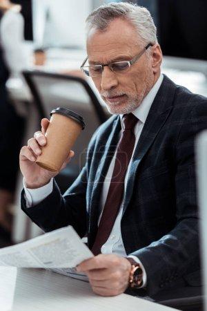 Photo pour Homme d'affaires beau regardant le journal tout en retenant la tasse jetable - image libre de droit