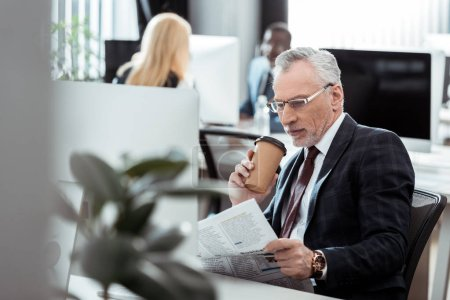 Photo for Selective focus of handsome businessman reading newspaper while holding disposable cup near multicultural coworkers - Royalty Free Image