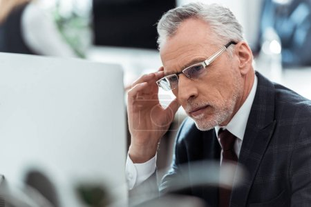 selective focus of mature businessman touching glasses in office