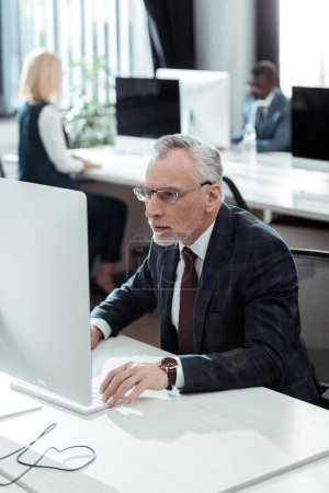 Photo for Selective focus of handsome mature businessman in glasses looking at computer monitor near multicultural colleagues in office - Royalty Free Image
