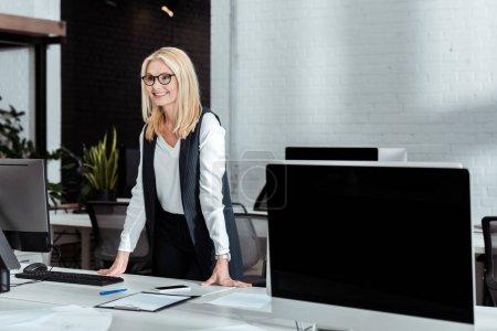 Photo pour Femme d'affaires blonde gaie dans des lunettes debout près du bureau dans le bureau - image libre de droit