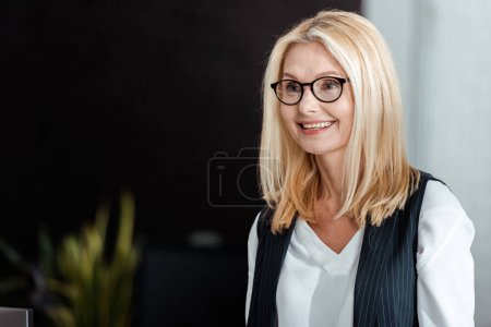 happy blonde and attractive businesswoman in glasses smiling in office