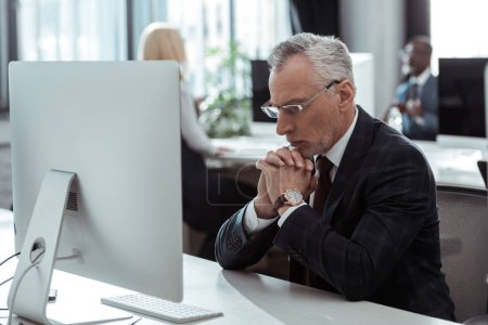 Photo for Selective focus of pensive mature businessman in glasses sitting near computer monitor and multicultural colleagues in office - Royalty Free Image