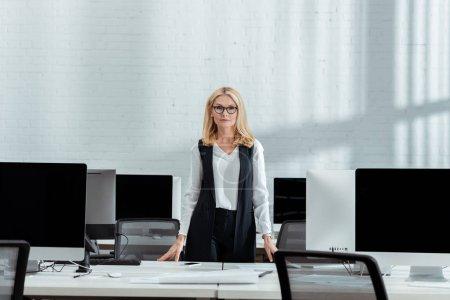 Photo pour Attrayant blonde femme d'affaires debout près des écrans d'ordinateur avec des écrans vides dans le bureau - image libre de droit