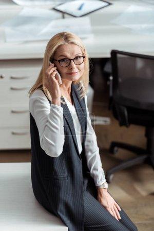 Photo pour Vue aérienne de femme d'affaires attrayante parlant sur smartphone - image libre de droit