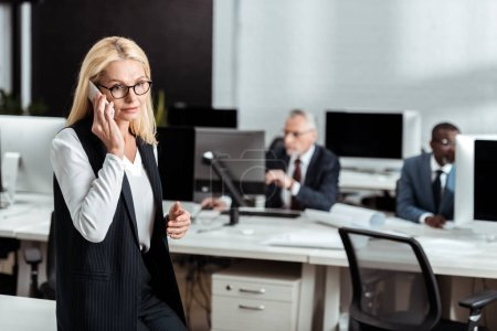 Photo for Selective focus of attractive businesswoman in glasses talking on smartphone near multicultural men - Royalty Free Image