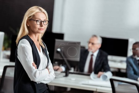 Photo for Selective focus of attractive businesswoman in glasses standing with crossed arms near multicultural men - Royalty Free Image