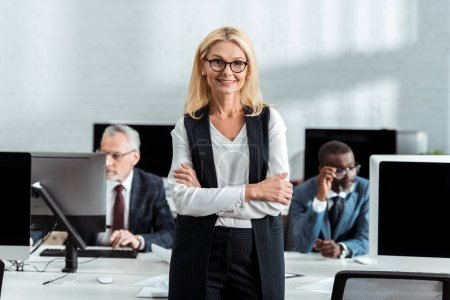 Photo for Selective focus of cheerful businesswoman standing with crossed arms near multicultural men in office - Royalty Free Image