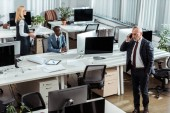 """Постер, картина, фотообои """"overhead view of businessman talking on smartphone near multicultural coworkers in office """""""
