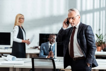 Photo for Businessman talking on smartphone near multicultural coworkers in office - Royalty Free Image