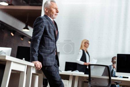 Photo pour Vue à faible angle de l'homme d'affaires se tenant près de collègues multiculturels dans le bureau - image libre de droit
