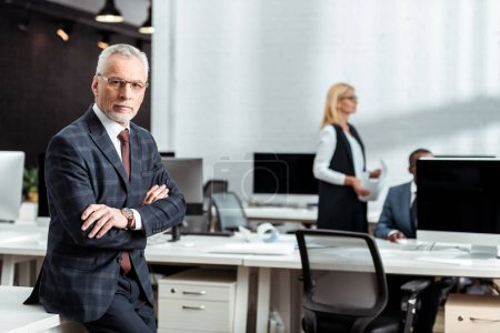 Photo for Selective focus of businessman in glasses looking at camera while standing with crossed arms in office - Royalty Free Image
