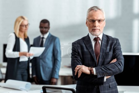 Photo pour Selective focus of confident businessman in glasses and looking at camera while standing with crossed arms near colleagues - image libre de droit