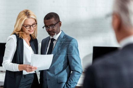 Photo for Selective focus of cheerful businesswoman and african american businessman looking at document near partner - Royalty Free Image