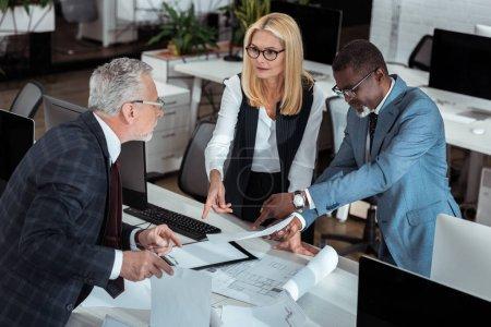 Photo pour Vue au-dessus de la femme d'affaires faisant des gestes près des plans et de l'homme d'affaires américain africain tout en regardant le associé - image libre de droit