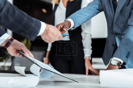 Photo pour Vue recadrée de l'homme afro-américain prenant stylo près du partenaire tenant presse-papiers - image libre de droit
