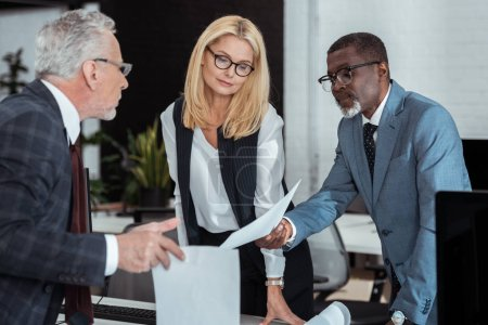 Photo for Selective focus of attractive businesswoman looking at paper near multicultural partners - Royalty Free Image