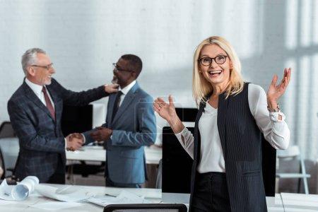Photo pour Foyer sélectif de femme d'affaires heureuse faisant des gestes près des hommes d'affaires multiculturels se serrant la main dans le bureau - image libre de droit