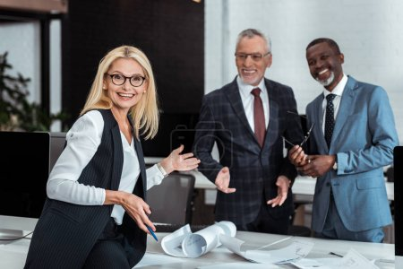 Photo for Selective focus of excited  businesswoman gesturing near multicultural businessmen in office - Royalty Free Image