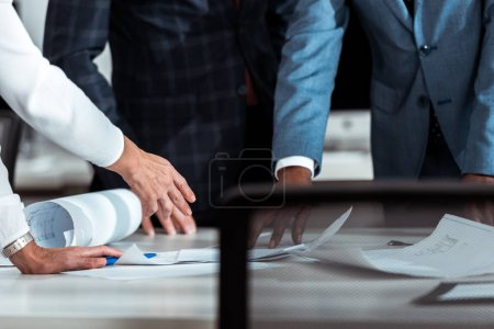 Photo pour Vue recadrée d'hommes d'affaires multiculturels et femme d'affaires debout près des plans - image libre de droit