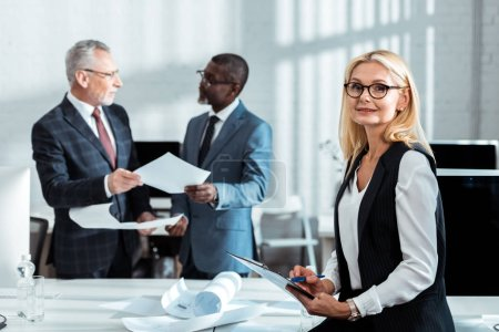 Photo for Selective focus of businesswoman in glasses holding clipboard near multicultural businessmen - Royalty Free Image