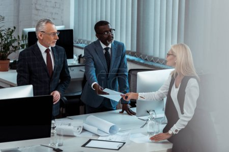 Photo pour African american business man giving blank paper to attractive blonde salope woman near partner in office - image libre de droit