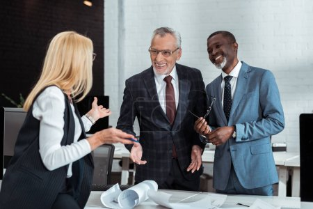 Photo for Selective focus of cheerful multicultural businessmen smiling while looking at blonde partner - Royalty Free Image