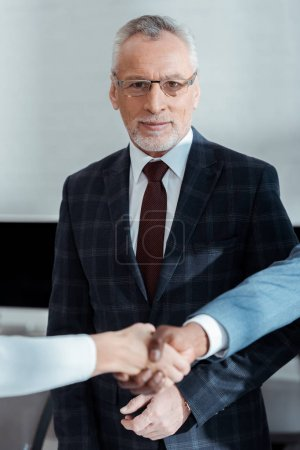 Photo for Selective focus of happy businessman looking at camera while african american man and woman shaking hands in office - Royalty Free Image