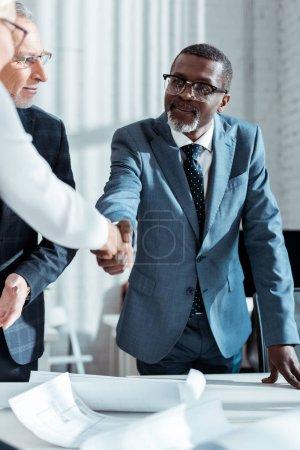 Photo pour Foyer sélectif de l'homme d'affaires dans des glaces regardant l'homme américain africain se serrant la main avec la femme dans le bureau - image libre de droit