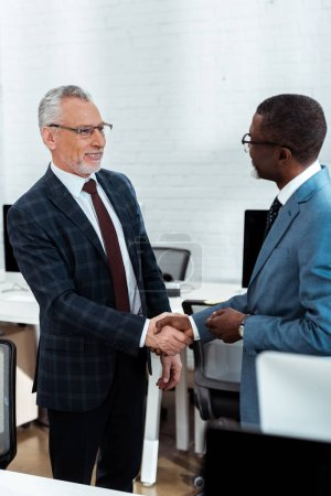 Photo for Selective focus of cheerful businessman in glasses shaking hands with african american partner - Royalty Free Image