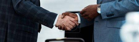 Photo pour Tir panoramique de l'homme d'affaires américain africain serrant la main avec le partenaire - image libre de droit