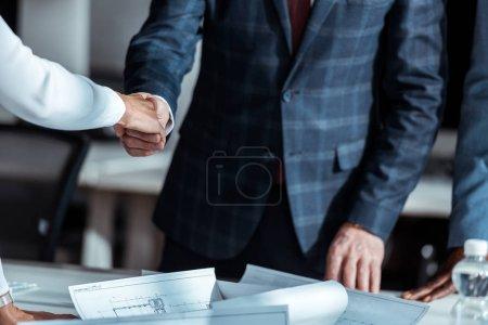 Photo pour Vue recadrée de femme d'affaires et d'homme d'affaires se serrant la main près du partenaire américain africain - image libre de droit