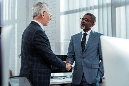 Photo pour Vue à faible angle des hommes d'affaires multiculturels se serrant la main dans le bureau - image libre de droit